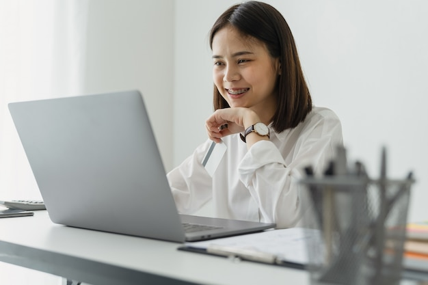 オフィスのテーブルの上のラップトップを使用してアジアの実業家。