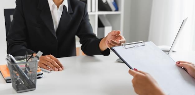 Бизнесмен в черном костюме сидит на офисе и стоять за руку, чтобы получить документы от персонала.
