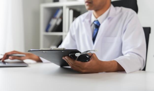 Доктор, держа файл отчета пациента для оценки симптомов на столе.