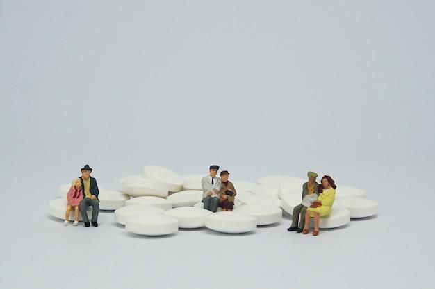 白い錠剤の山の上に座っている老夫婦家族図。