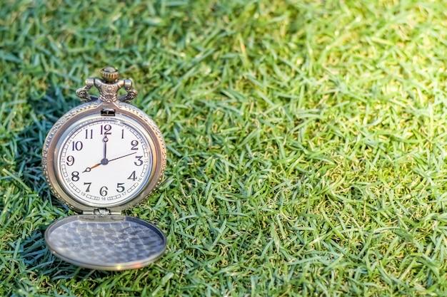 コピースペースと時間の概念のための抽象的な緑の芝生とビンテージポケットゴールドウォッチ