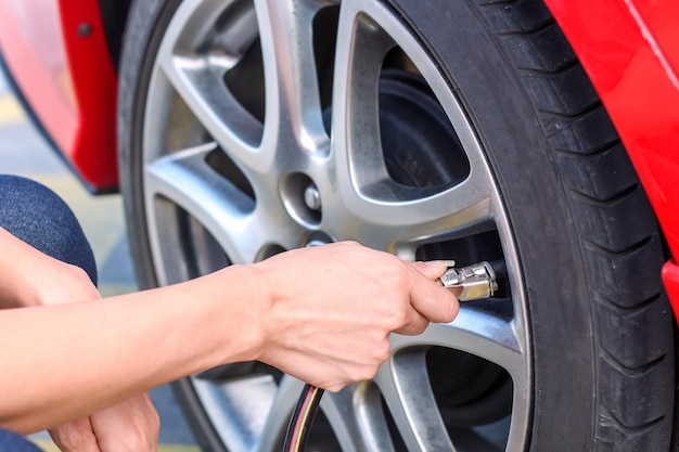 Женщина заправляет воздух в автомобильную шину, чтобы увеличить давление