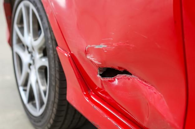赤い車のサイドドアの穴事故のクローズアップ