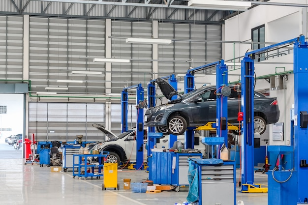 修理や修理されているガレージで持ち上げ装置で車