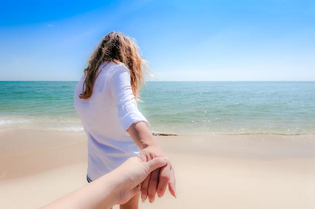 カップルがビーチで手をつないで散歩の背面図