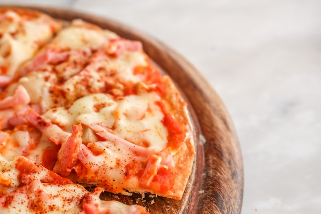 白い花こう岩の石のテーブルにチーズを溶かしたピザのスライス。