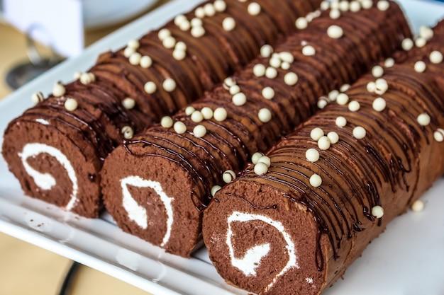 Закройте красивый шоколадный рулет ям в белой тарелке