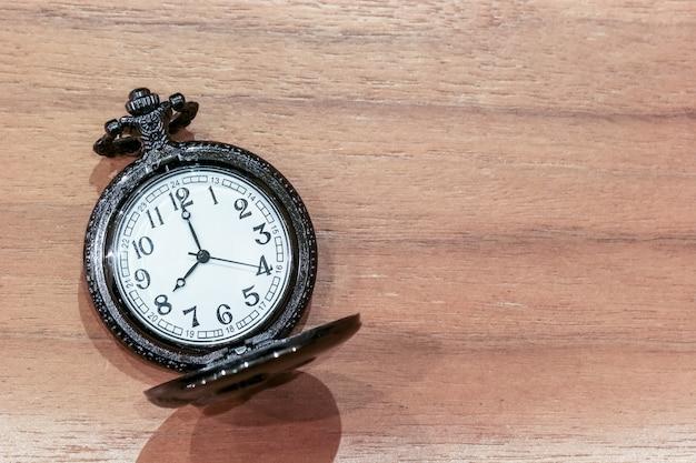 コピースペースを持つ木製テーブルの上の高級懐中時計