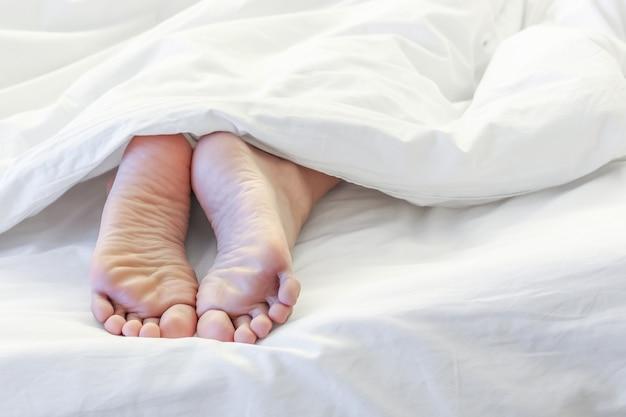 白いベッドの部屋で眠っている女性の足