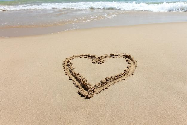 Форма сердца, символ любви, написанные на песчаном пляже