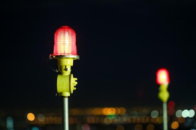 Макрофотография самолета предупреждение света на вершине высотного здания в ночное время