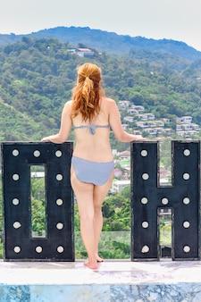 ビキニの女性はスイミングプールの端に立っています。