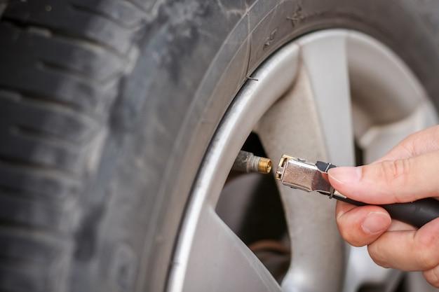 汚れた車のタイヤに空気を入れて圧力を高める