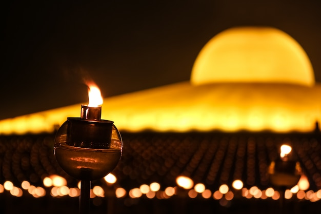 タイのダンマカヤ寺院でマカブチャの日に仏に敬意を表すろうそくの光。