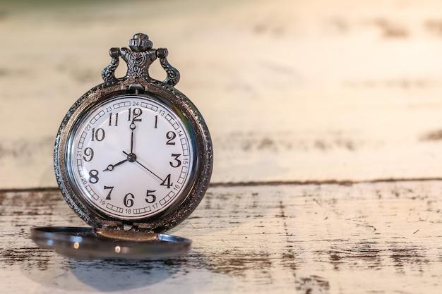 木製テーブルの上の豪華なヴィンテージブラック懐中時計