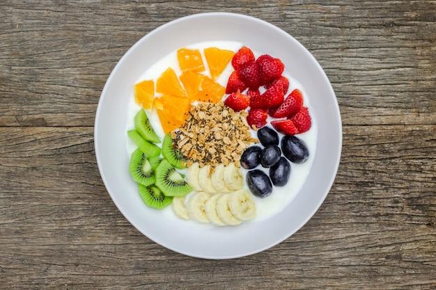 Тарелка натурального белого йогурта с мюсли, апельсин, банан, киви, клубника и виноград фрукты на деревянных фоне. йогурт и фрукты в качестве ингредиентов вокруг тарелки. вид сверху. здоровая концепция.