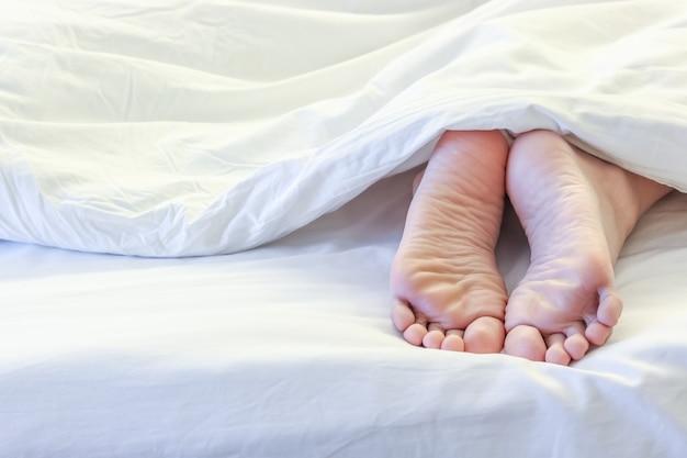 白いベッドルームで眠っている女性の足