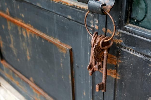 素朴なドアにいくつかの古いさびたキーチェーン