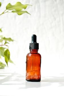 Бутылки ароматического масла с лепестками. основы ароматерапии. ботанический уход за кожей в домашних условиях санаторно-курортное лечение. вид сверху.