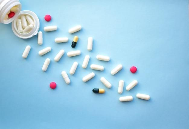 瓶から注ぐ各種医薬品錠剤とカプセル