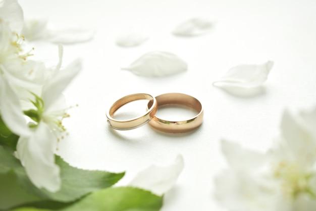 結婚指輪。白い背景の上と繊細な白い花。