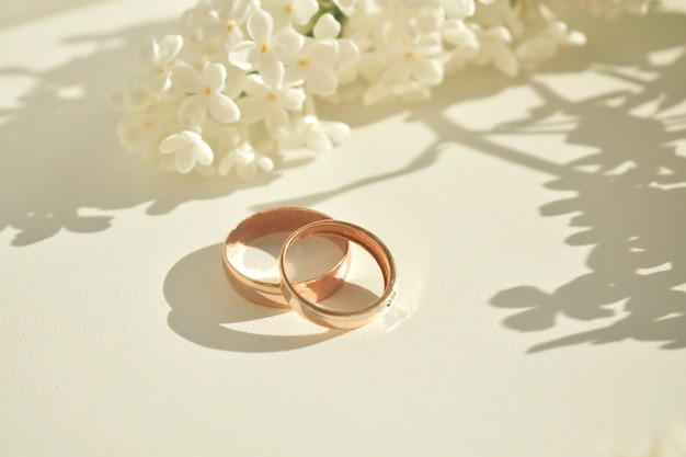Обручальное кольцо. на белом фоне и с нежными белыми цветами. свадебные символы и атрибуты