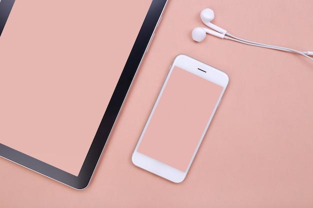 トップビューモックアップスマートフォンとタブレットのピンクのパステル調の背景