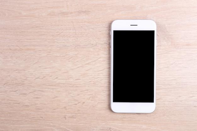 木製の背景にモックアップ画面のスマートフォン