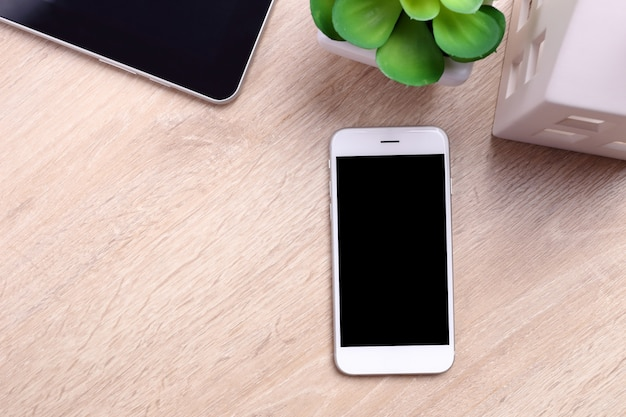 モックアップ画面のスマートフォン、タブレット、事務用品の木製の背景
