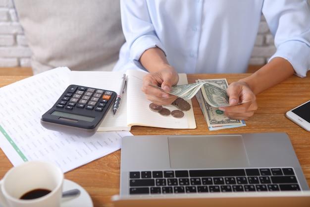 木製の机の上のラップトップおよびオフィスの文房具でお金を数えるビジネス女性