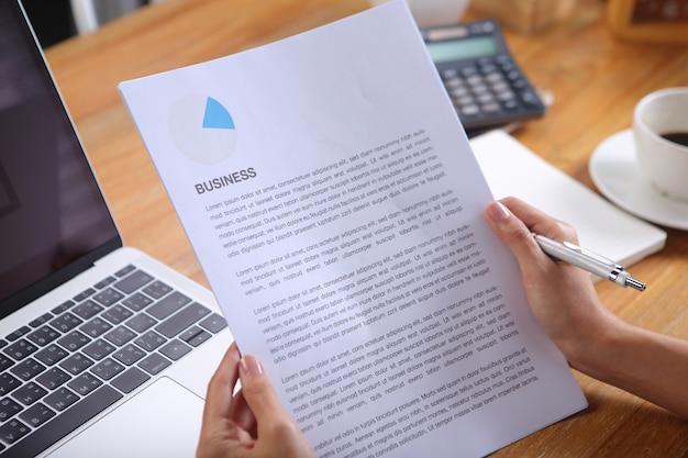 ノートパソコンと木製の机の上のブラックコーヒーとビジネスニュースを読むビジネス女性