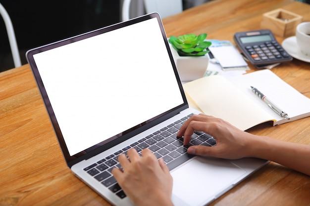 Коммерсантка используя компьтер-книжку макета с канцелярскими принадлежностями офиса на деревянном столе