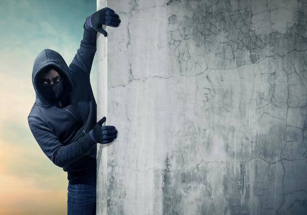 テキスト用のスペースを持つ空の壁の後ろに隠れている強盗