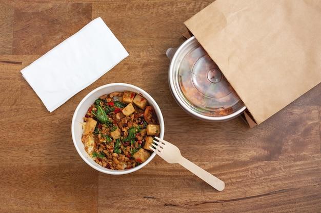 木製の背景の紙箱にご飯と豚肉とバジルの炒め物
