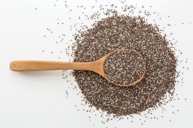 Семена чиа в деревянной ложкой на белом фоне