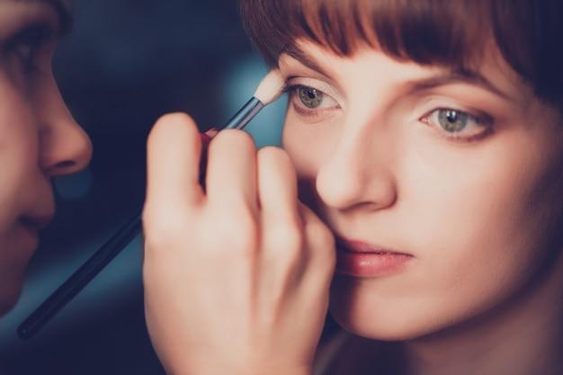 メイクアップアーティストによるメイクを適用する美しい少女をクローズアップ