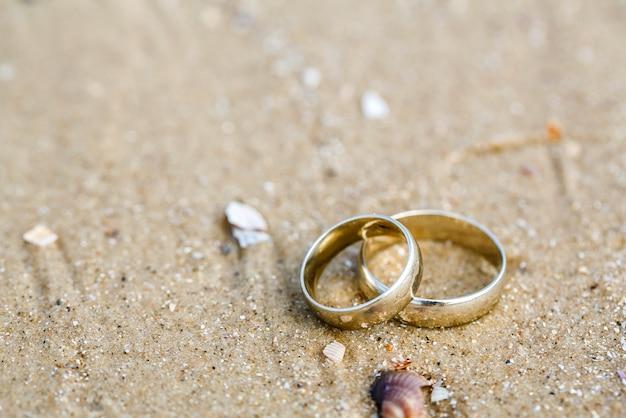 結婚式のコンセプト-結婚指輪は砂の上にあります。