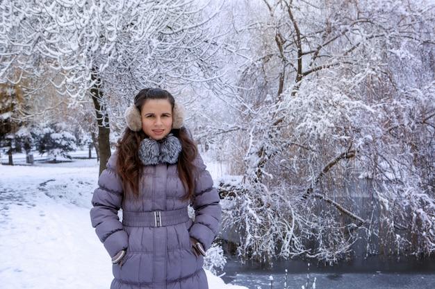 冬のイヤーマフの若い女性の肖像画は、冬の公園を歩いています。