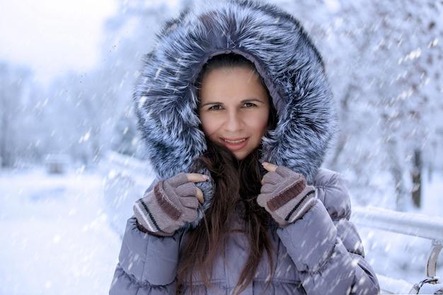 Портрет красивой зимней женщины в меховой шапке гуляет в парке