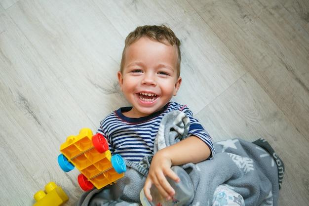床-平面図で笑って楽しんで幸せな小さな男の子