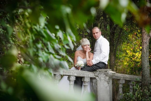 エレガントな花嫁と新郎の結婚式の日に屋外で一緒にポーズ