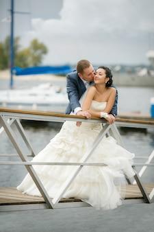 若いカップルは、花束のポーズで新郎新婦が大好きです。夏の結婚式の日。幸せと愛の瞬間を楽しんでいます。