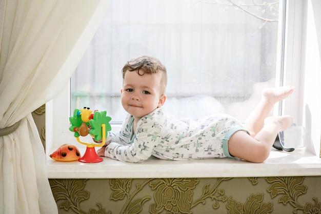 窓辺にかわいい小さな巻き毛の少年