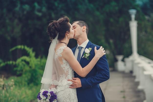 彼の幸せな豪華なブルネットの花嫁とエレガントなスタイリッシュな新郎
