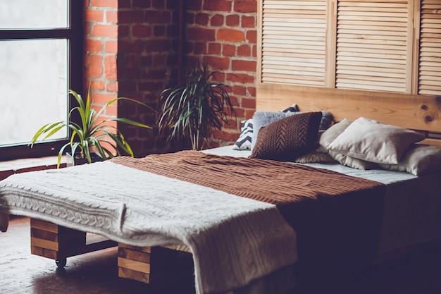 ダブルベッド、赤レンガの壁、大きな窓のあるシンプルなベッドルーム