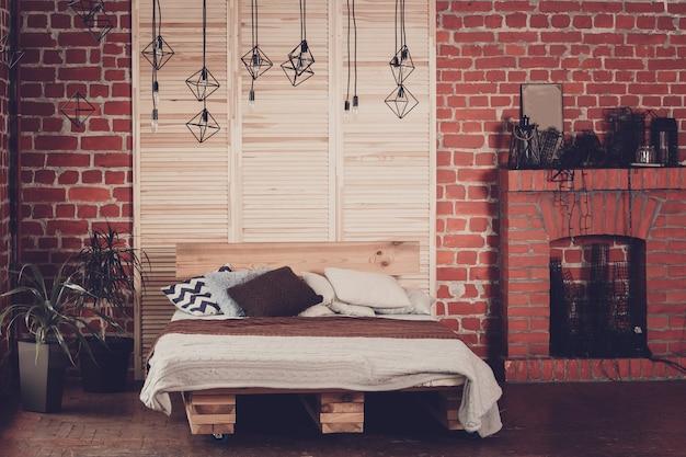 Простая спальня с двуспальной кроватью, красной кирпичной стеной и большим окном