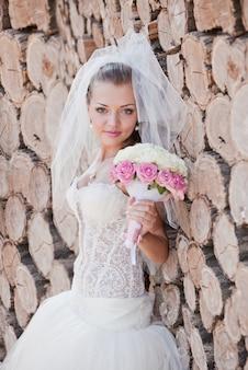 花嫁は丸太の近くに立っています。