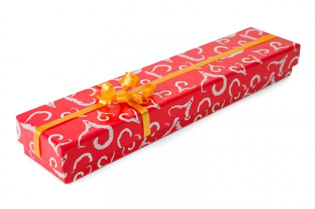 白で隔離されるオレンジ色のリボンと赤いギフトボックス