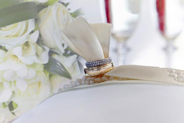 Обручальные кольца лежат на белой подушке крупным планом