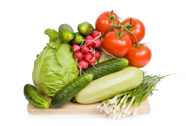 カラフルな野菜ボードと新鮮な野菜。白で隔離されます。